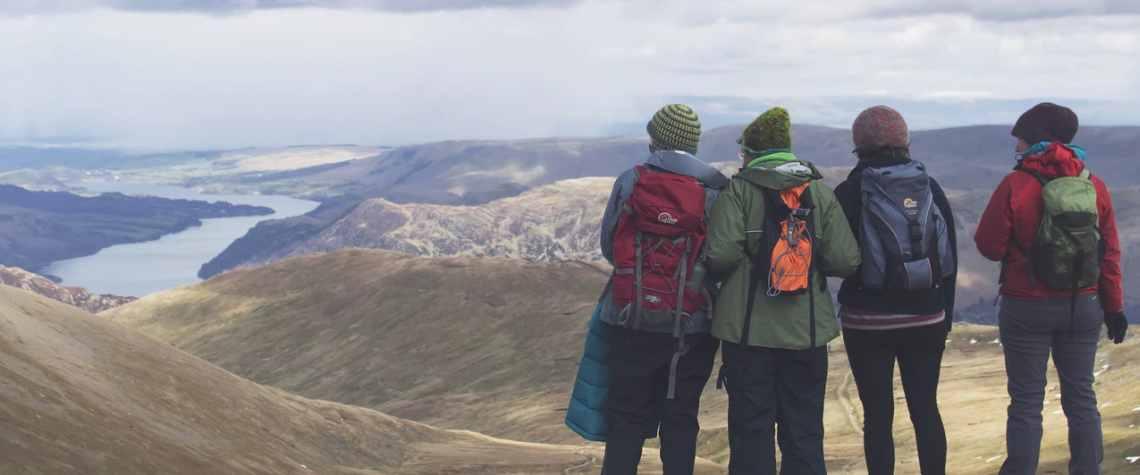 Chicos visitando una montaña y contemplando el horizonte